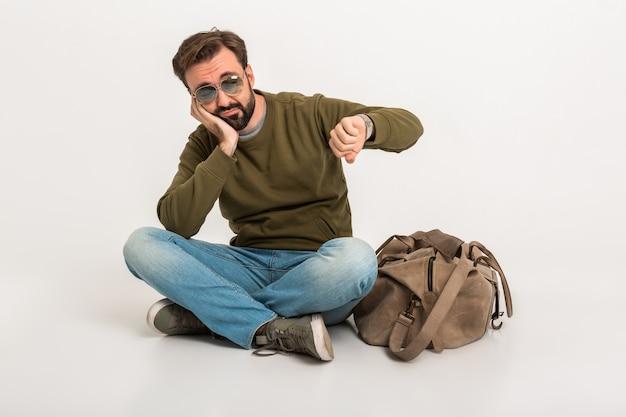 Podróżnik atrakcyjny mężczyzna na białym tle czeka smutny