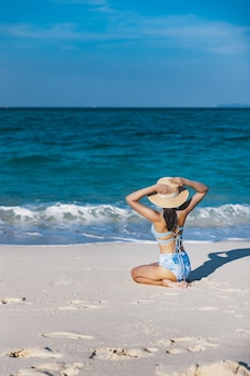 Podróżnik azjatycka kobieta z bikini i kapeluszem relaks na plaży w dzień w koh lipe, satun, tajlandia