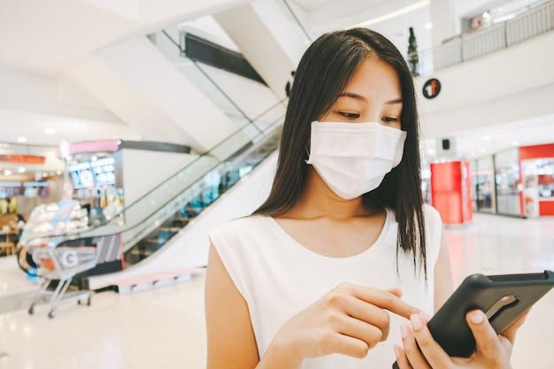 Podróżnik azjatykcia kobieta z maską i telefonem komórkowym w zakupy centrum handlowym dla nowego normall stylu życia pojęcia