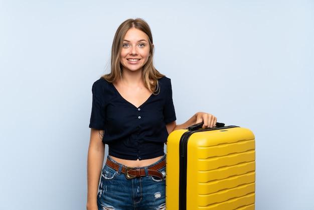 Podróżnik blondynki kobieta z walizką z niespodzianką i zszokowanym wyrazem twarzy