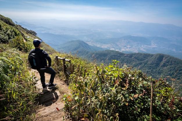 Podróżnik człowiek stojący i patrząc obfitość widok na naturalny las tropikalny w górach.