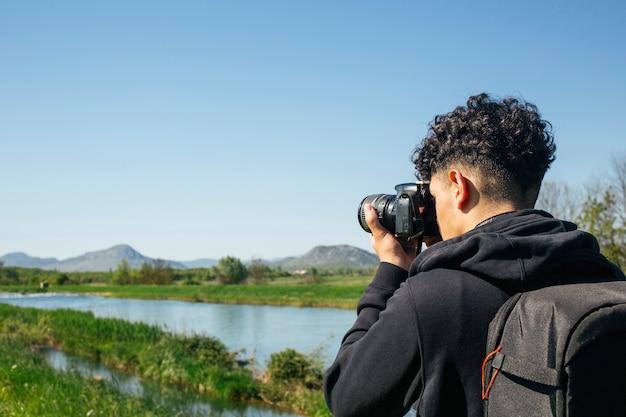Podróżnik fotograf robi zdjęcie z plecakiem do noszenia