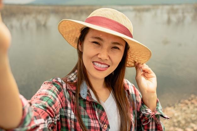 Podróżnik kobieta bierze selfie przy jeziorem w lato czasie.
