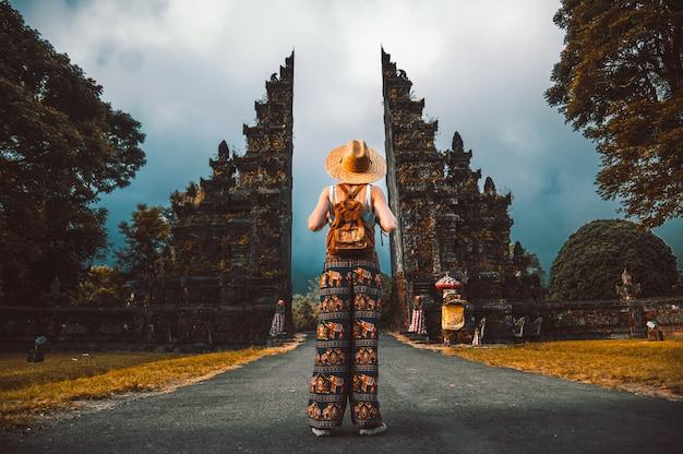 Podróżnik kobieta pozuje przed świątynią w bali, indonezja. kobieta z plecakiem na wycieczce w azji