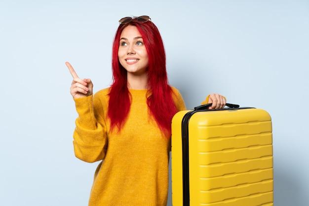 Podróżnik kobieta trzyma walizkę odizolowywająca na błękit ścianie wskazuje w górę doskonałego pomysłu