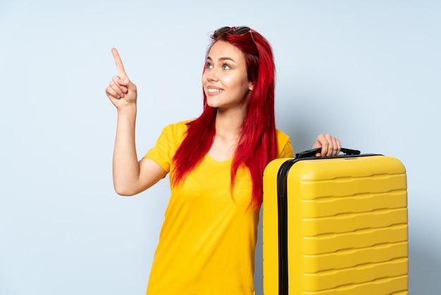 Podróżnik kobieta trzyma walizkę odizolowywająca na błękit ścianie wskazuje z palcem wskazującym świetny pomysł