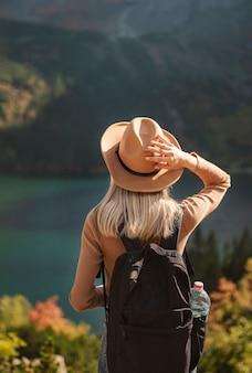 Podróżnik kobieta w kapeluszu i patrząc na niesamowite góry i jezioro, koncepcja podróży wanderlust. lake morskoy eye w polskich tatrach.