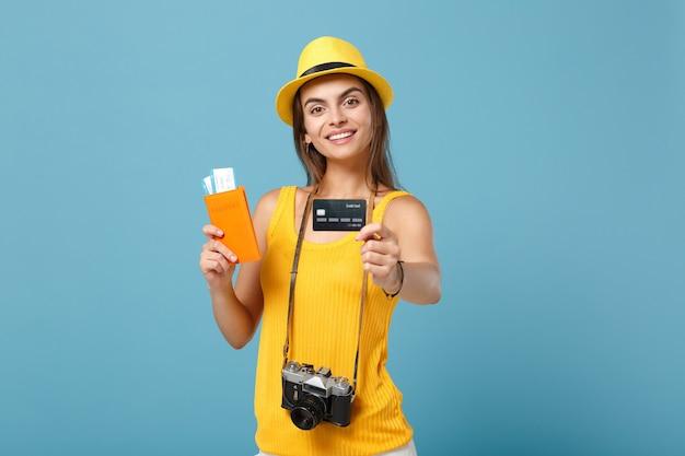 Podróżnik kobieta w żółtym kapeluszu ubrania trzymająca bilety na kartę kredytową aparat na niebiesko