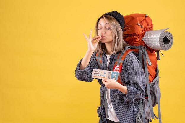 Podróżnik kobieta z plecakiem trzymająca bilet co kucharz całuje znak