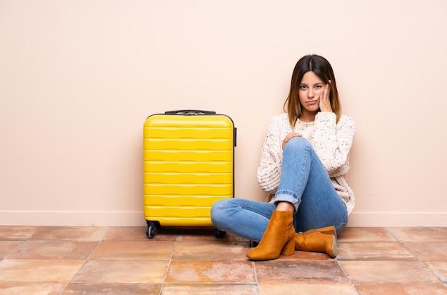Podróżnik kobieta z walizką siedzi na podłodze nieszczęśliwy i sfrustrowany