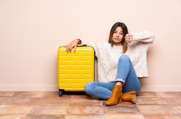 Podróżnik kobieta z walizki obsiadaniem na podłoga pokazuje kciuka puszka znaka