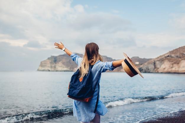 Podróżnik kobiety bieg wzdłuż brzeg rewolucjonistki plaża na santorini wyspie, grecja. koncepcja podróży i wakacji