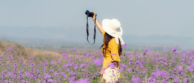 Podróżnik lub turystyka azjatyckie kobiety stojąc i trzymając aparat fotograficzny kwiat na fioletowym polu werbeny