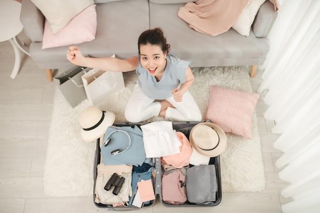 Podróżnik, ludzie, turystyka i koncepcja wakacje. szczęśliwa kobieta gotowa do podróży z walizką