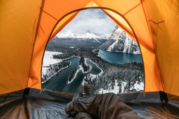 Podróżnik mężczyzna odpoczywa i cieszy się widokiem na zaśnieżoną górę i jezioro w pomarańczowym namiocie na zimę w parku narodowym yoho, kanada