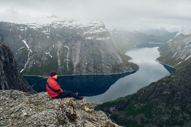 Podróżnik mężczyzna relaksująca medytacja z spokojnymi widok górami i jezioro krajobrazem podróżuje styl życia wycieczkuje pojęcie wakacji tła plenerowi