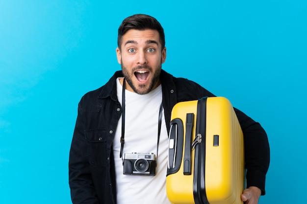 Podróżnik mężczyzna trzyma walizkę na niebiesko z zaskoczenia i zszokowany wyraz twarzy