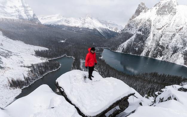 Podróżnik mężczyzna w czerwonej kurtce stojący na szczycie płaskowyżu opabin w śnieżycy w parku narodowym yoho, kanada