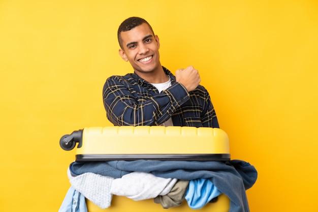 Podróżnik mężczyzna z walizką pełną ubrań na pojedyncze żółte ściany świętuje zwycięstwo