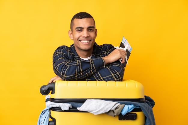 Podróżnik mężczyzna z walizką pełną ubrań na pojedyncze żółte ściany