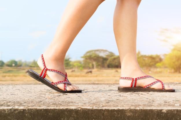 Podróżnik młode kobiety na sneakers kują odprowadzenie na moscie na słonecznym dniu