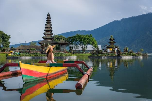 Podróżnik młodej kobiety brodzik na drewnianej łodzi w pura ulun danu bratan