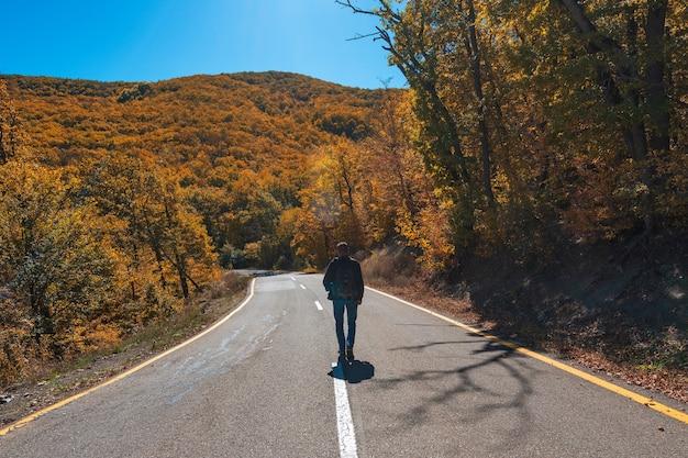 Podróżnik na drodze wśród żółtego jesiennego górskiego lasu