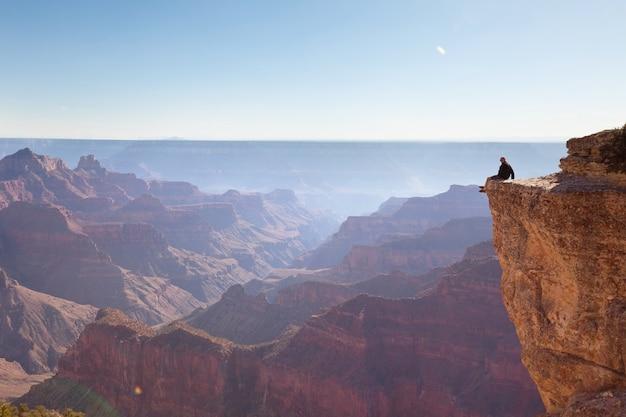 Podróżnik na klifach nad parkiem narodowym wielkiego kanionu, arizona, usa. inspirujące emocje. podróż styl życia podróż sukces motywacja koncepcja przygoda wakacje koncepcja na świeżym powietrzu.