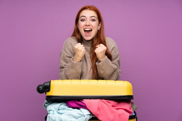 Podróżnik nastolatka dziewczyna z walizką pełną ubrań świętuje zwycięstwo