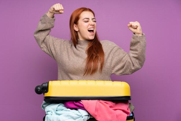 Podróżnik nastolatka kobieta z walizką pełną ubrań świętuje zwycięstwo