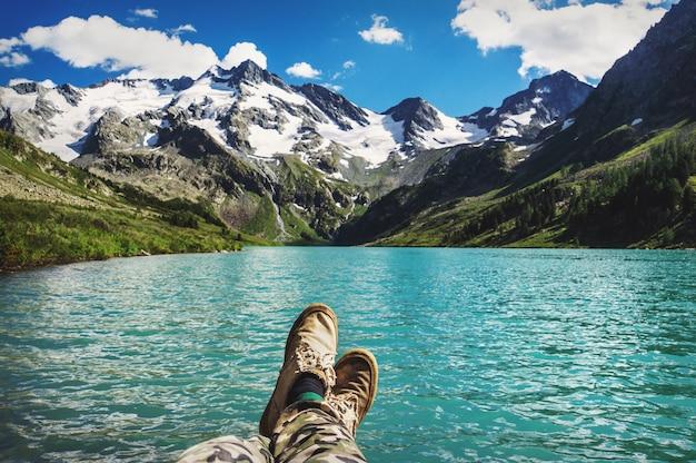 Podróżnik odpoczywa na płaskowyżu górskim. widok pov, nogi z bliska na tle górskiego krajobrazu z pięknym turkusowym jeziorem