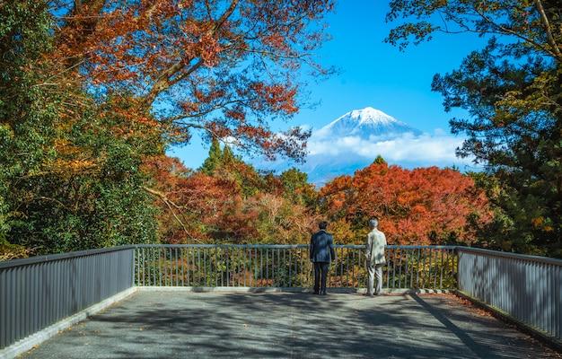 Podróżnik patrzeje mt fuji i kolorowy jesień liść przy shiraito spada w fujinomiya, shizuoka, japonia.
