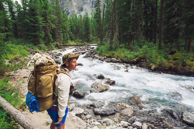 Podróżnik po drodze wzdłuż górskiej rzeki. szybki strumień wody w dzikiej górskiej zatoczce.