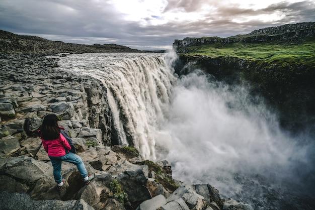 Podróżnik podróżuje do wodospadu dettifoss na islandii
