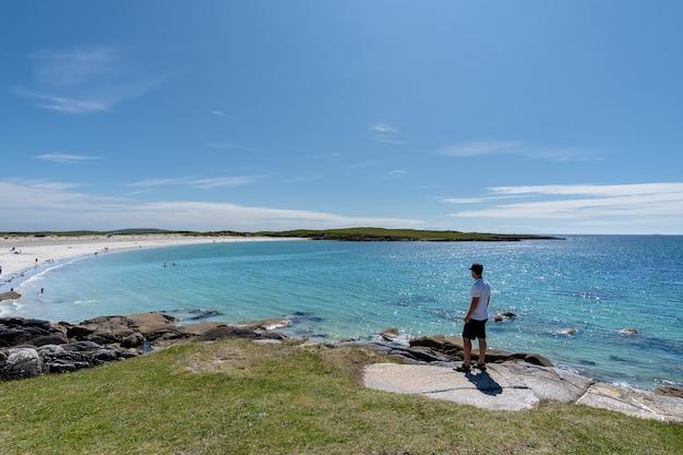 Podróżnik podziwiający zapierające dech w piersiach krajobrazy na plaży dogs bay w galway w irlandii