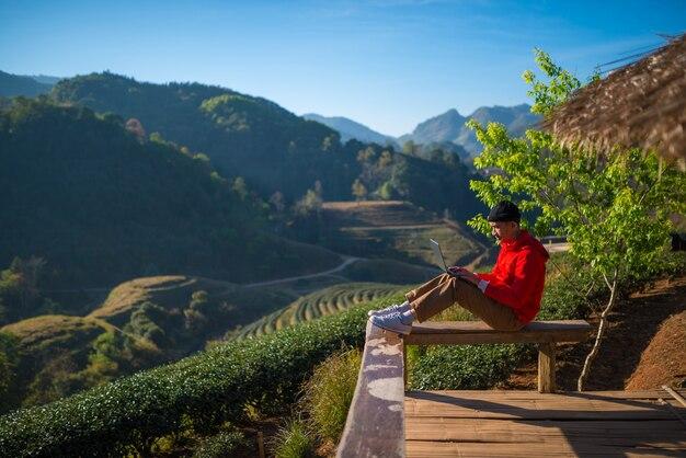 Podróżnik rano gra na laptopie z widokiem na górski krajobraz, sieć, komunikację