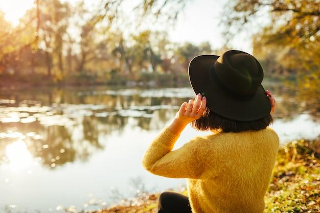 Podróżnik relaksuje jesieni rzeką przy zmierzchem