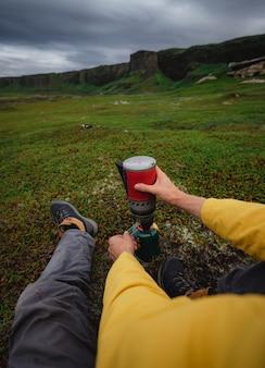 Podróżnik robi kawę na czerwonym palniku gazowym turystycznym w rosyjskiej północnej tundrze. półwysep kolski