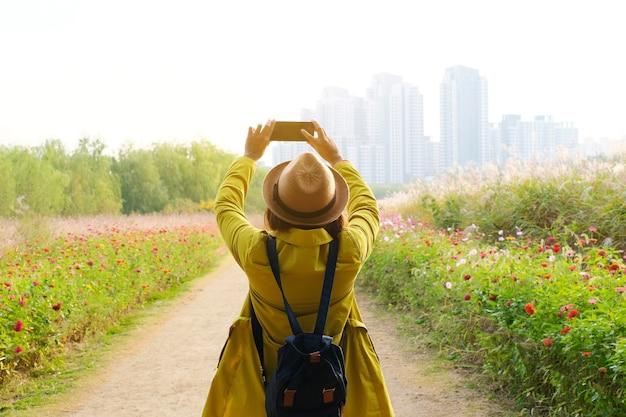 Podróżnik robi zdjęcie w pięknym parku z budynkami w tle.