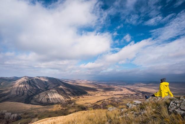Podróżnik siedzi jesienią na wzgórzu i niewielkiej górze i spogląda w dal