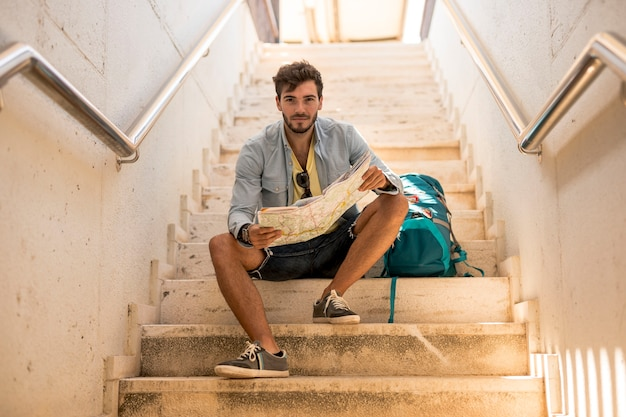 Podróżnik siedzi na schodach patrząc na kamery