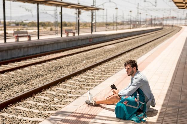 Podróżnik siedzi na ziemi w stacji kolejowej