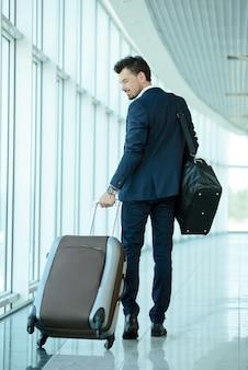 Podróżnik służbowy ciągnie walizkę i trzyma paszport.