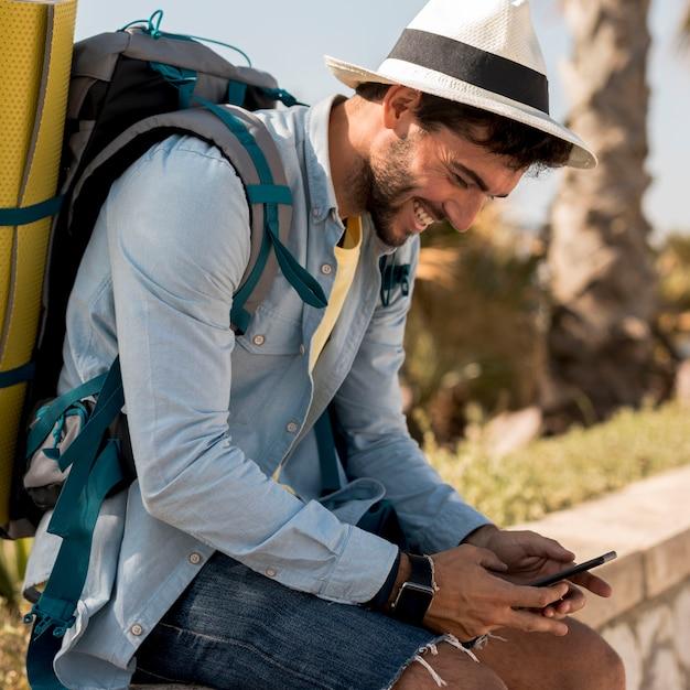 Podróżnik smilling przy smartphone