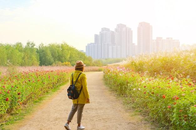 Podróżnik spacerujący po parku kwiatowym do budynku w seulu korea