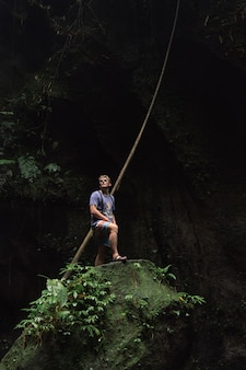 Podróżnik stoi na krawędzi omszałego kamienia w jaskini bali indonezja