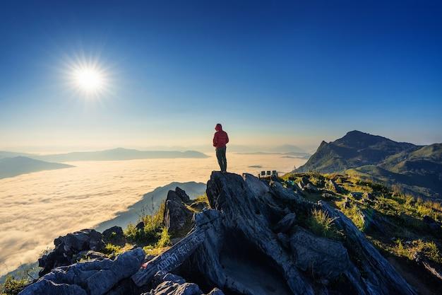 Podróżnik stojący na skale, doi pha tang i porannej mgle w chiang rai w tajlandii.