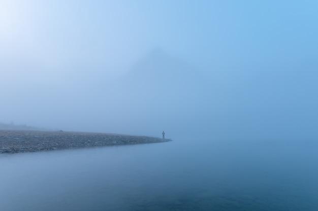 Podróżnik stojący samotnie w niebieskiej mgle ze skalistymi górami nad jeziorem rano