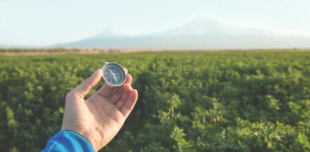 Podróżnik trzymając kompas na zewnątrz.
