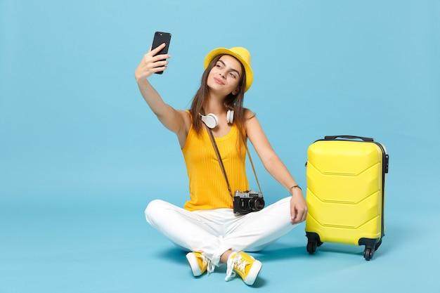 Podróżnik turysta kobieta w żółtych ubraniach casual, kapelusz z walizkowym aparatem fotograficznym na niebiesko